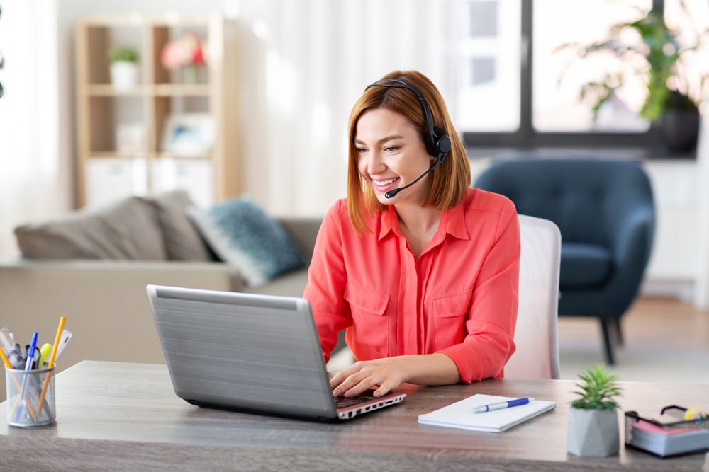 woman working from home with laptop and headset