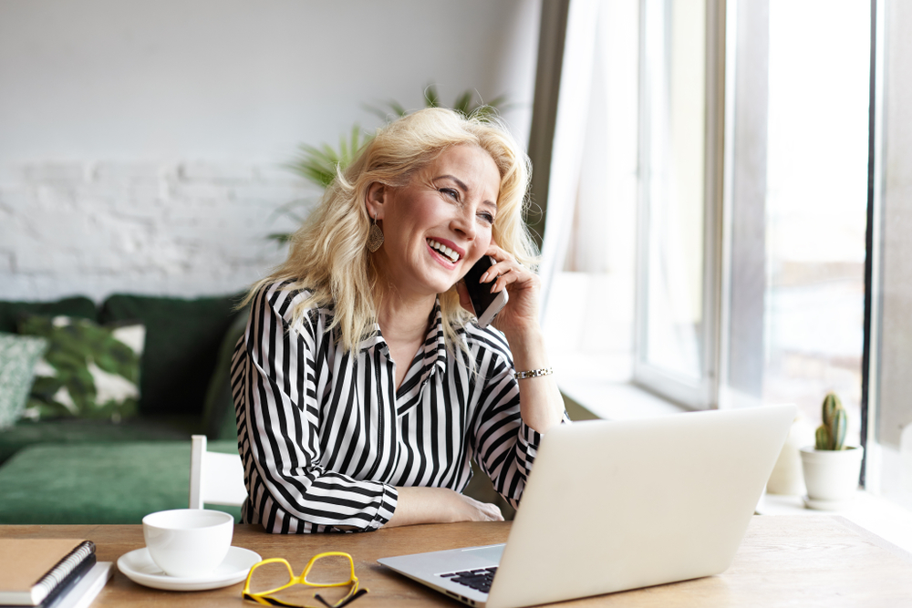 business professional talking on phone in home office