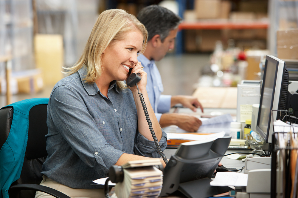 woman talking on desk phone in office setting