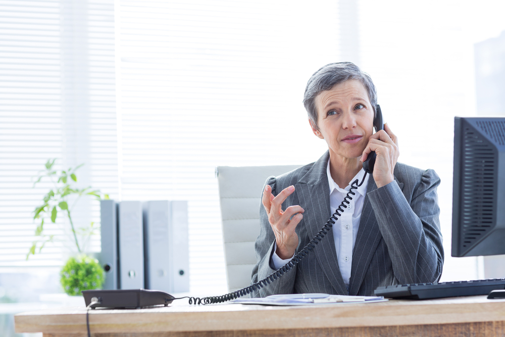 business woman wearing suit on phone in corporate office