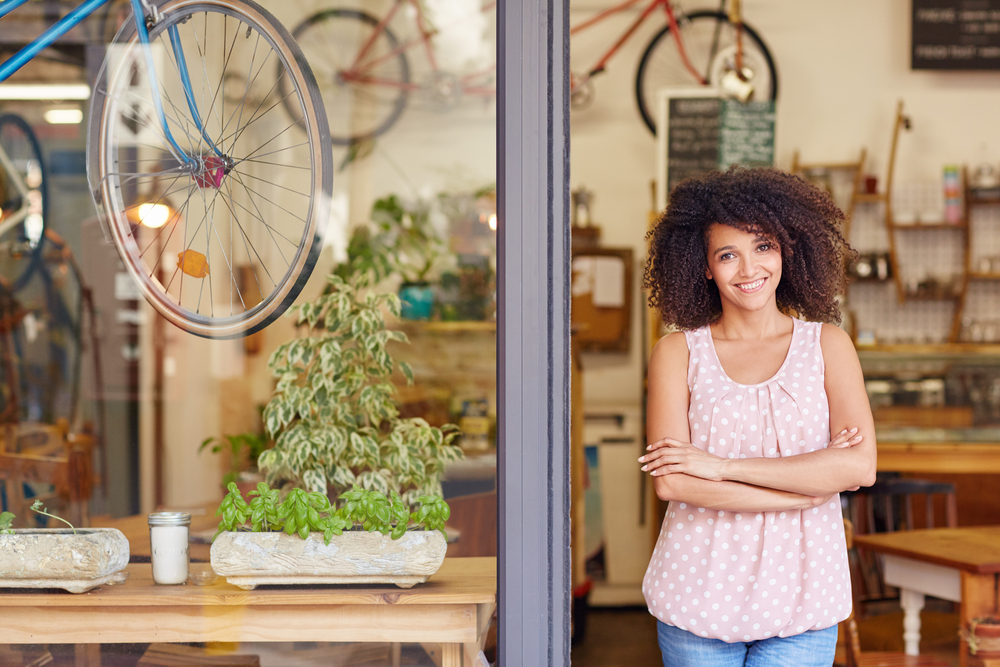 female small business owner standing outside of her retail shop with for a new EAS detection system